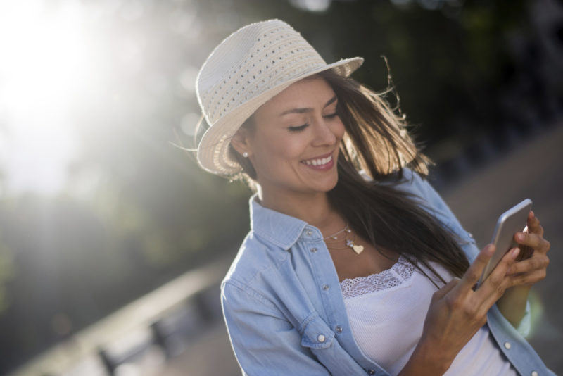 Beautiful summer woman in her 20s texting on her cell phone outdoors and looking very happy